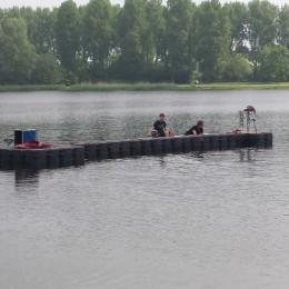 Waterscherm op pontons wordt afgemeerd